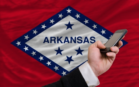 telecommuniation: man holding cell phone in front flag of us state of arkansas symbolizing mobile communication and telecommunication