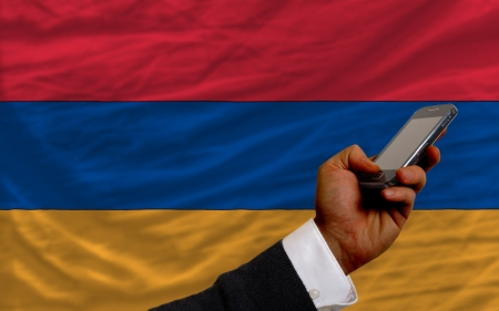 man holding cell phone in front national flag of armenia symbolizing mobile communication and telecommunication