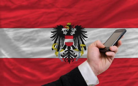 telecommuniation: man holding cell phone in front national flag of austria symbolizing mobile communication and telecommunication