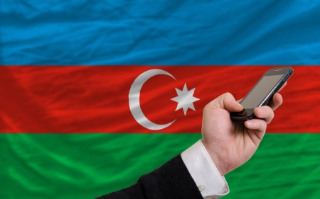 telecommuniation: man holding cell phone in front national flag of azerbaijan symbolizing mobile communication and telecommunication