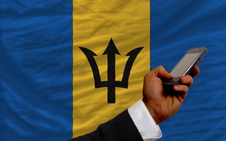 telecommuniation: man holding cell phone in front national flag of barbados symbolizing mobile communication and telecommunication