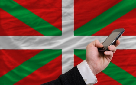 man holding cell phone in front national flag of  basque symbolizing mobile communication and telecommunication