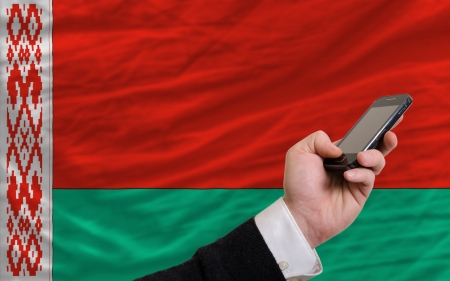 telecommuniation: man holding cell phone in front national flag of belarus symbolizing mobile communication and telecommunication Stock Photo