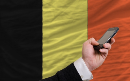 telecommuniation: man holding cell phone in front national flag of belgium symbolizing mobile communication and telecommunication