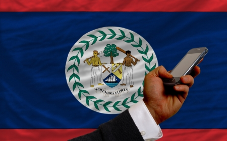 telecommuniation: man holding cell phone in front national flag of belize symbolizing mobile communication and telecommunication
