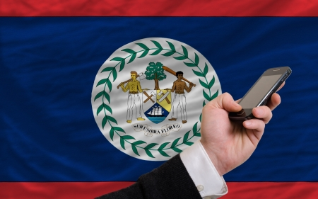 man holding cell phone in front national flag of belize symbolizing mobile communication and telecommunication