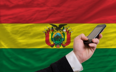 man holding cell phone in front national flag of bolivia symbolizing mobile communication and telecommunication