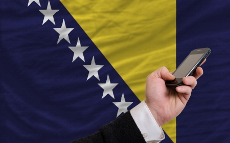 telecommuniation: man holding cell phone in front national flag of bosnia herzegovina symbolizing mobile communication and telecommunication Stock Photo
