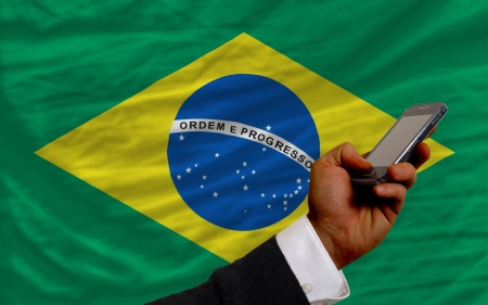 telecommuniation: man holding cell phone in front national flag of brazil symbolizing mobile communication and telecommunication