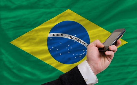 man holding cell phone in front national flag of brazil symbolizing mobile communication and telecommunication