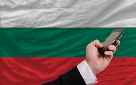 man holding cell phone in front national flag of bulgaria symbolizing mobile communication and telecommunication Stock Photo - 17921484