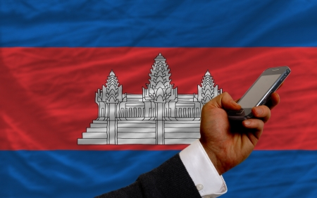 man holding cell phone in front national flag of cambodia symbolizing mobile communication and telecommunication