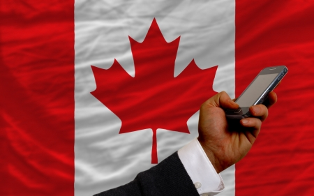 telecommuniation: man holding cell phone in front national flag of canada symbolizing mobile communication and telecommunication