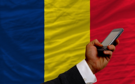 chadian: man holding cell phone in front national flag of  chad symbolizing mobile communication and telecommunication Stock Photo