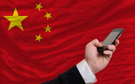 man holding cell phone in front national flag of china symbolizing mobile communication and telecommunication