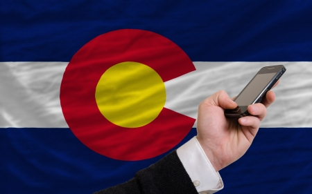 man holding cell phone in front flag of us state of colorado symbolizing mobile communication and telecommunication