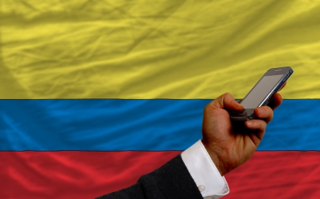man holding cell phone in front national flag of columbia symbolizing mobile communication and telecommunication