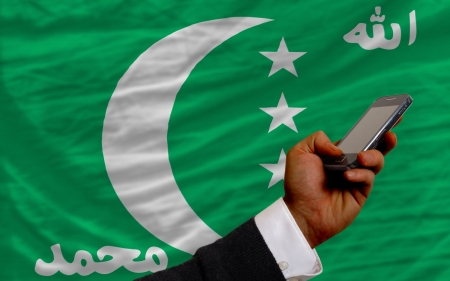 man holding cell phone in front national flag of  comoros symbolizing mobile communication and telecommunication Stock Photo