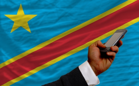 telecommuniation: man holding cell phone in front national flag of  congo symbolizing mobile communication and telecommunication