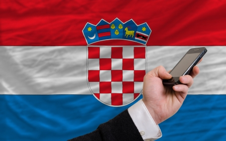 telecommuniation: man holding cell phone in front national flag of croatia symbolizing mobile communication and telecommunication