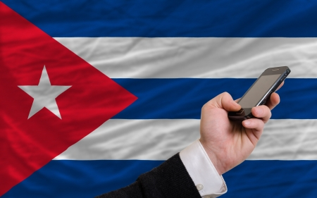 telecommuniation: man holding cell phone in front national flag of cuba symbolizing mobile communication and telecommunication