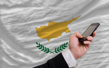 man holding cell phone in front national flag of cyprus symbolizing mobile communication and telecommunication Stock Photo - 17921427