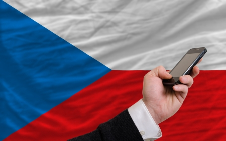 telecommuniation: man holding cell phone in front national flag of czech symbolizing mobile communication and telecommunication Stock Photo