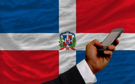 telecommuniation: man holding cell phone in front national flag of dominican symbolizing mobile communication and telecommunication Stock Photo