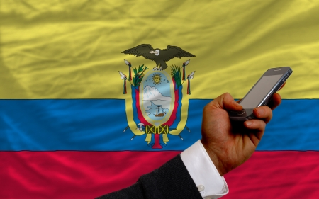 telecommuniation: man holding cell phone in front national flag of ecuador symbolizing mobile communication and telecommunication