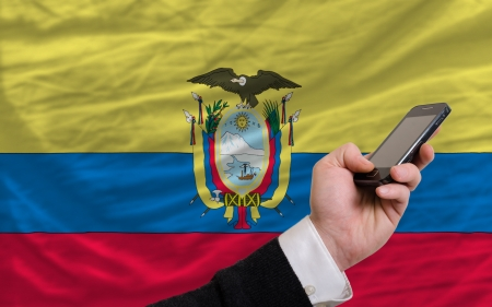 man holding cell phone in front national flag of ecuador symbolizing mobile communication and telecommunication