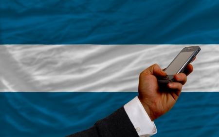 telecommuniation: man holding cell phone in front national flag of el salvador symbolizing mobile communication and telecommunication