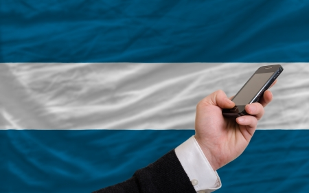man holding cell phone in front national flag of el salvador symbolizing mobile communication and telecommunication Stock Photo - 17921425