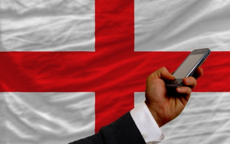 telecommuniation: man holding cell phone in front national flag of england symbolizing mobile communication and telecommunication Stock Photo