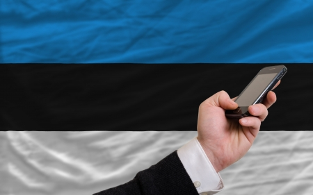 telecommuniation: man holding cell phone in front national flag of estonia symbolizing mobile communication and telecommunication Stock Photo