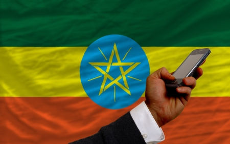 man holding cell phone in front national flag of ethiopia symbolizing mobile communication and telecommunication