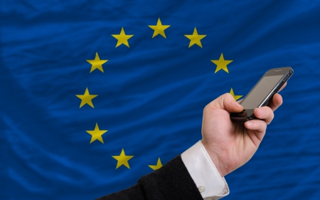 man holding cell phone in front national flag of europe symbolizing mobile communication and telecommunication