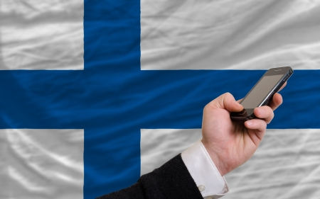 telecommuniation: man holding cell phone in front national flag of finland symbolizing mobile communication and telecommunication