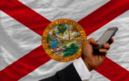 telecommuniation: man holding cell phone in front flag of us state of florida symbolizing mobile communication and telecommunication