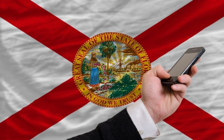 man holding cell phone in front flag of us state of florida symbolizing mobile communication and telecommunication