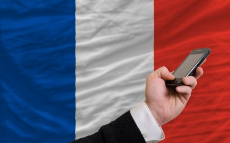 telecommuniation: man holding cell phone in front national flag of france symbolizing mobile communication and telecommunication Stock Photo
