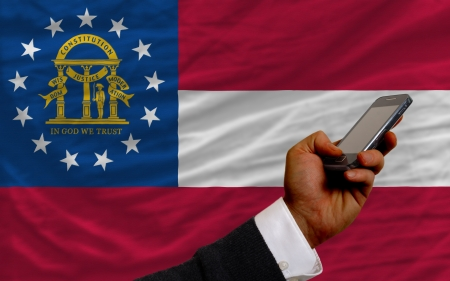 man holding cell phone in front flag of us state of georgia symbolizing mobile communication and telecommunication