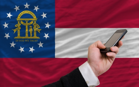 telecommuniation: man holding cell phone in front flag of us state of georgia symbolizing mobile communication and telecommunication