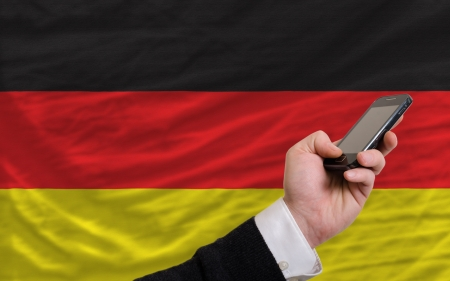 telecommuniation: man holding cell phone in front national flag of germany symbolizing mobile communication and telecommunication