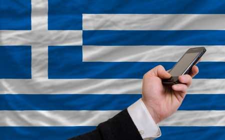 man holding cell phone in front national flag of greece symbolizing mobile communication and telecommunication Stock Photo - 17921440