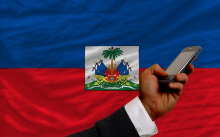 telecommuniation: man holding cell phone in front national flag of haiti symbolizing mobile communication and telecommunication