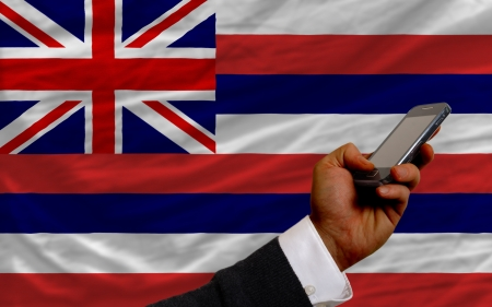 telecommuniation: man holding cell phone in front flag of us state of hawaii symbolizing mobile communication and telecommunication