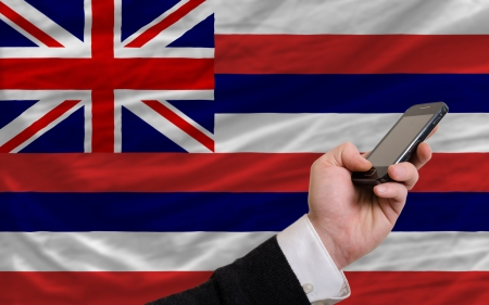 man holding cell phone in front flag of us state of hawaii symbolizing mobile communication and telecommunication