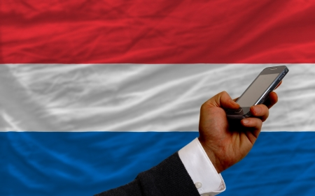 man holding cell phone in front national flag of netherlands symbolizing mobile communication and telecommunication Stock Photo - 17921501