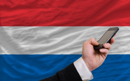 man holding cell phone in front national flag of netherlands symbolizing mobile communication and telecommunication Stock Photo - 17921499