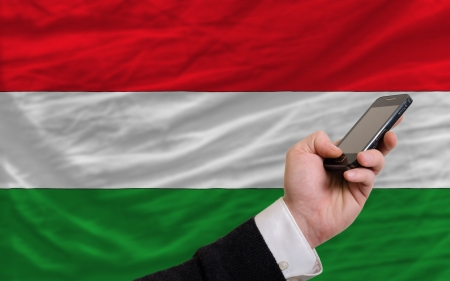 telecommuniation: man holding cell phone in front national flag of hungary symbolizing mobile communication and telecommunication